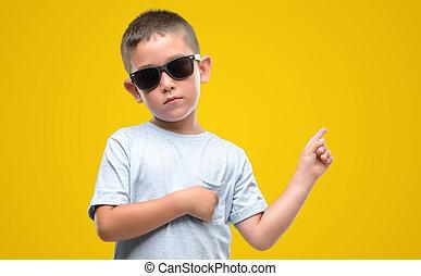 haired oscuro, niño pequeño, llevar lentes de sol, muy, feliz, señalar, con, mano, y, dedo, al lado