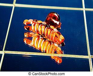 Orange hairpin on mirror table
