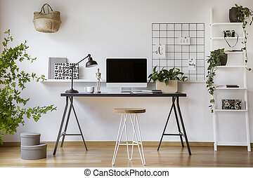 Hairpin stool standing by the wooden desk with mockup computer screen, metal lamp and coffee cup in real photo of white home office interior