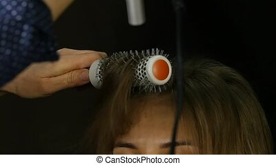 Hairs Blow-Drying. Hairdresser drying client hair with...