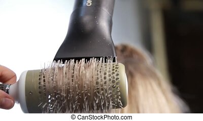 Hairs blow-drying, the best technique. Salon hair treatment by well qualified hairdresser