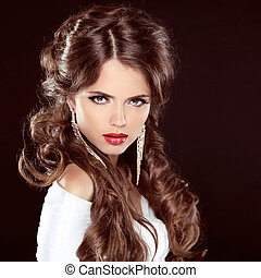 Hairstyle. Beautiful Girl Portrait. Beauty Woman with brown curly long hair styling over dark. Red Lips