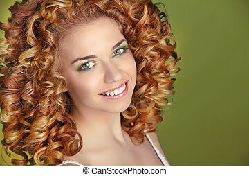 Hairstyle. Curly Hair. Attractive smiling girl portrait on green background. Glossy Smooth Fashion Hair. Extensions