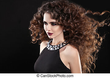 Hairstyle. Fashion brunette girl with Long curly hair, beauty makeup. Glamour portrait of beautiful woman with marsala matte lips, blowing hairstyle isolated on black background.