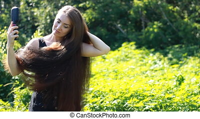 Young beautiful woman with very long hair. Cute girl combs comb brown hair.