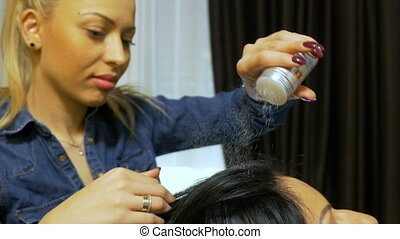 Hairstylist applying styling powder on client's hair at...