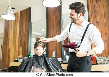 Hairstylist Combing Hair Of Boy In Barber Shop