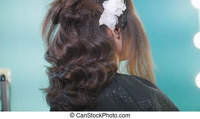 Hairstylist creating complicated evening hairstyle, close up