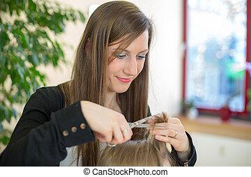 Hairstylist cutting customers hair