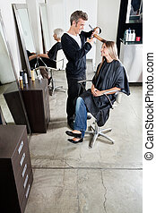 Hairstylist Cutting Customer's Hair In Salon