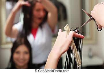 Hairstylist cutting hair in salon