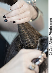 hairstylist cutting hair of female customer