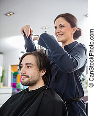 Hairstylist Cutting Male Client's Hair In Salon