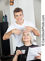 Hairstylist Cutting Woman's Hair In Salon