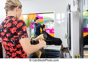 Hairstylist Drying Customer's Hair With Blow Dryer