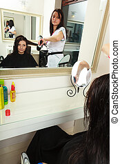 Hairstylist drying hair woman client in hairdressing beauty salon