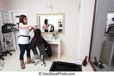 Hairstylist drying hair woman salon