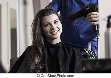 Hairstylist drying woman's hair