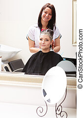 Hairstylist dyeing hair woman client in hairdressing beauty salon