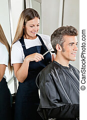 Hairstylist Giving Haircut To Client At Salon
