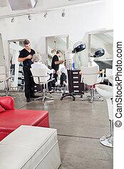 Hairstylist Ironing Customer's Hair - Male hairstylist...