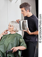 Hairstylist Showing Finished Haircut To Customer