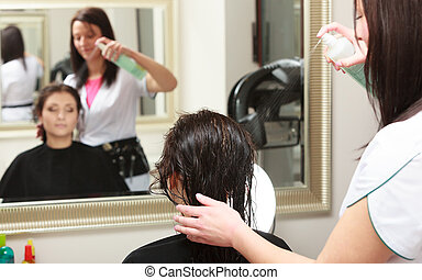 Hairstylist spraying hair woman client in hairdressing beauty salon