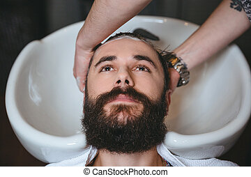 Hairstylist washing head of man with beard in barbershop