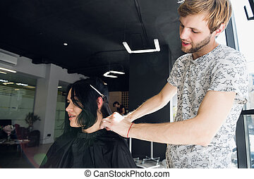 Hairstylist with comb and scissors cutting hair of female client. Woman in hairdressing beauty salon.