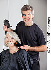 Hairstylist With Dryer Setting Up Woman's Hair