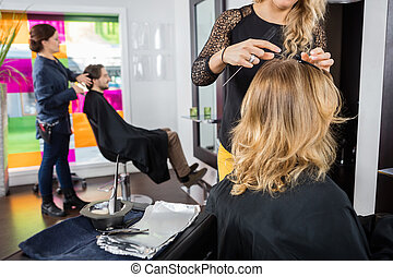 Hairstylist Working On Customer's Hair In Parlor