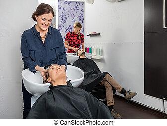 Hairstylists Washing Customers Hair At Salon