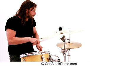 Hairy drummer playing his drum kit on white background