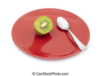 Half a fresh kiwi on a plate with a spoon