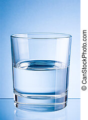 Half a glass of drinking water on blue background