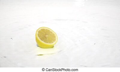 Half a lemon drops into the water. White background. Slow motion