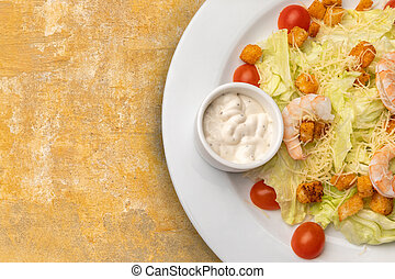 half a plate of Caesar salad on textured table