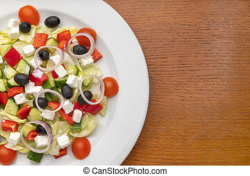 half a plate of salad on a wooden table