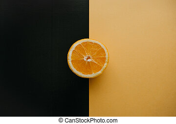 Half an orange on a black and yellow background