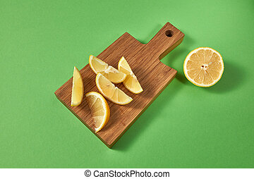 Half and slices of fresh tropical yellow lemon on a wooden cutting brown board. View from above. Citrus fruits on a green background with place for text.