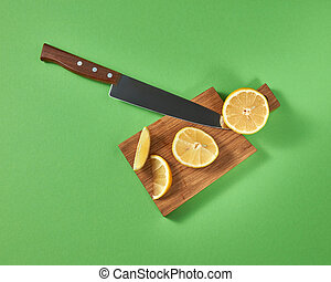 Half and slices of fresh tropical yellow lemon on a wooden cutting brown board with a steel knife. View from above.