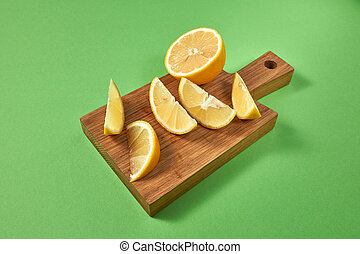 Half and slices of natural organic yellow lemon on a wooden brown board. View from above. Juicy citrus fruits on a green background.