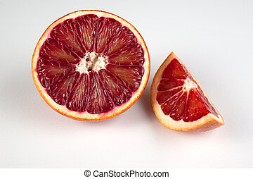 half and wedge of red blood sicilian orange isolated on white