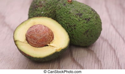 Half and Whole Avocados on Wood - Close up dolly shot of...