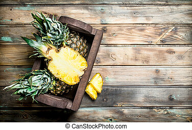 Half and whole pineapples in the box.