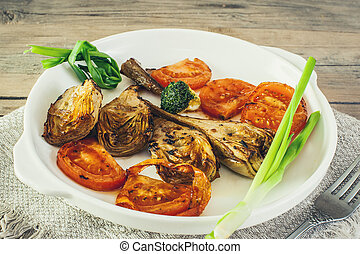 half artichoke, grilled and served with slices of ripe red tomatoes, Brussels sprouts and green onions on a white plate on a wooden background in rustic style.