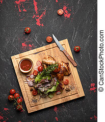 Half baked grilled chicken with fresh salad and sauce on black kitchen table. Appetizing meat dish on cutting board. Blank for restaurant advertising banner. High angle view. Vertical format 4x5