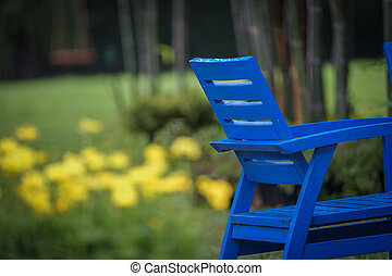 half blue chair in the garden with blur yellow flower at the background.