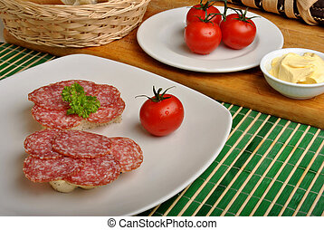 half bread roll with salami on a plate