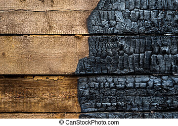 Half charred wooden wall of the house, contrast